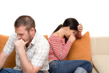 pareja-indiferente-ella-llora-el-piensa-sillon-cojines-naranjas